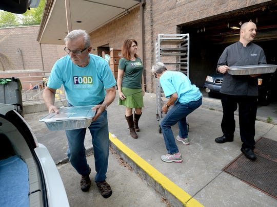 Jim Creel, left, loads a tray of food into his car as he, his wife Nancy, center right, and Flori Pate, executive director of Food Connection, center left, pick up food from UNC Asheville campus dining executive chef Alex Williams on Thursday, April 21, 2016. The University is a regular donator of extra food and one of several that have made up the 20,000 meals Food Connection has been able to supply to those in need since starting 17 months ago. That particular donation was going to feed people at the East Asheville Welcome Table.