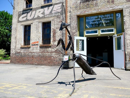 A praying mantis sculpture sits outside of Curve Studios in the River Arts District. The city will get easements to the property at the corner of Riverside Drive and Lyman Street as part of the RADTIP road improvement project.
