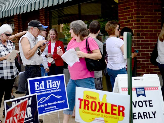 Senator Terry Van Duyn, center in red, talks with voters as they wait at the Enka-Candler Public Library to cast their ballots on the first day of early voting on Thursday, Oct. 20, 2016.