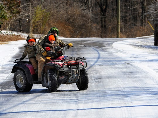 Joseph Abernathy rides a four-wheeler with his sons