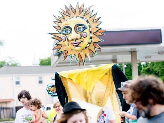 A sun puppet floats above the parade during the Appalachian