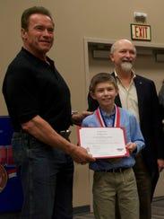 Jacob Littler receives a scholarship certificate from