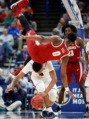 Alabama's Donta Hall (0) flips over Auburn's Chuma