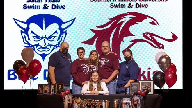 Sault High's Aliah Robertson, front row, has signed with Southern Illinois University. Pictured, back row, from left to right: Sault HIgh swimming and diving coach Steve Habusta, Ali's mother Shari Robertson, sister Melina Robertson and father Todd Robertson, and Sault coach Allison Innerebner.