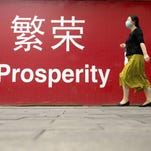 """A woman walks in July past a banner reading """"Prosperity"""" in English and Chinese on a street in central Beijing."""