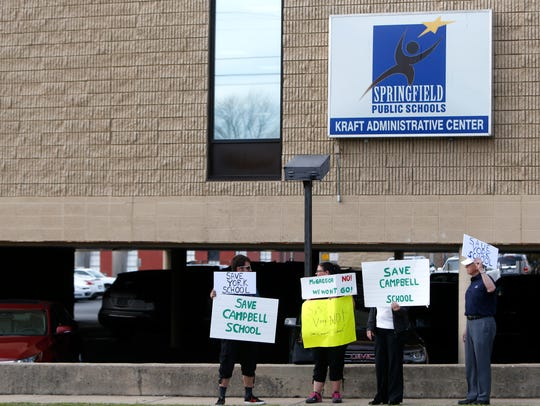 Protestors stand outside the Kraft Administration Center