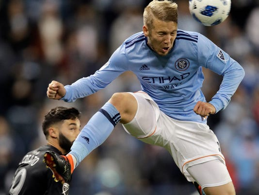 New York City midfielder Alexander Ring (8) heads the ball away from Sporting Kansas City forward Cristian Lobato (19) during the first half of an MLS soccer match in Kansas City, Kan., Sunday, March 4, 2018. (AP Photo/Orlin Wagner)