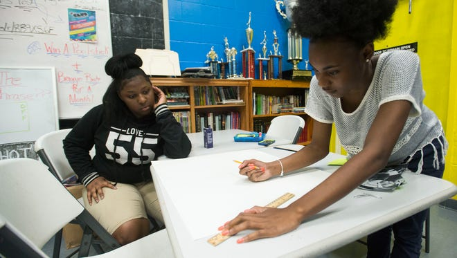 LaJazmond Wilson, right, helps Alysia English, left, with a homework assignment while the two girls attend the Boys and Girls Club Wednesday afternoon.