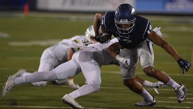 Nevada's Wyatt Demps sheds a couple of tacklers while taking on Cal Poly defenders during the Wolf Pack's season opener.