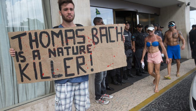 """A protester holds a banner that reads: """"Thomas Bach is a Nature Killer"""" as police guard the entrance of the hotel where International Olympic Committee meeting in Rio de Janeiro, Brazil, Saturday, Feb. 28, 2015."""
