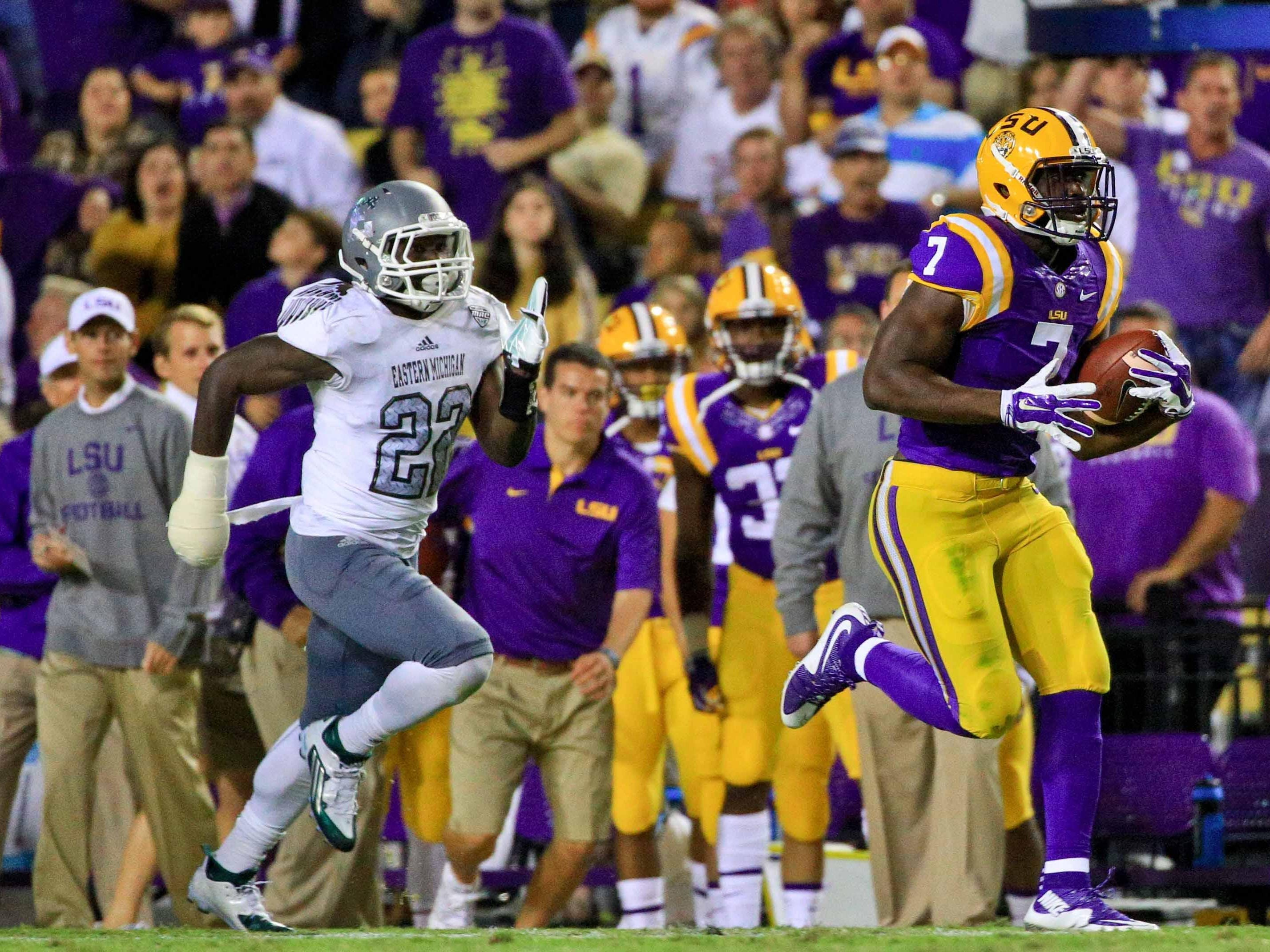 LSU Tigers running back Leonard Fournette (7) breaks away from Eastern Michigan Eagles defensive back Anthony Brown (22) running for a 75-yard touchdown during the third quarter of a game at Tiger Stadium.