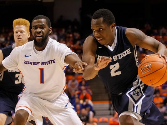 Utah State's Darius Perkins (2) drives the ball around Boise State's Mikey Thompson (1) during the second half of an NCAA college basketball game in Boise, Idaho, on Saturday, Jan. 3, 2015. Utah State won 62-61. (AP Photo/Otto Kitsinger)