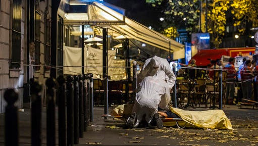 FILE - This is a Friday, Nov. 13, 2015 file photo of Investigating police officers inspect the lifeless body of a victim of a shooting attack outside the Bataclan concert hall in Paris, France. Sunday marks the anniversary of the  Nov. 13, deadly attacks  in Paris.