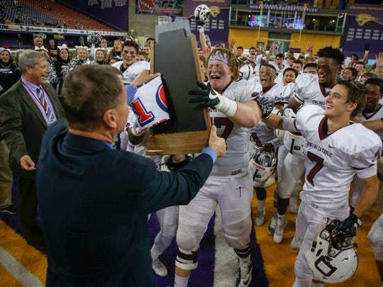 Dowling Catholic senior offensive tackle Peter Nank is emotional as he reaches for the Class 4A state championship trophy on Nov. 18, 2016.