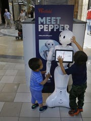 James Mak, left, and Marco Mak touch Pepper the robot at Westfield Valley Fair shopping center in San Jose, Calif. Pepper greets shoppers and has the potential to send messages geared to people's age and gender through facial recognition. A San Francisco supervisor is calling for a tax on robots that automate jobs and put people out of work, saying the money should be used to help the unemployed.