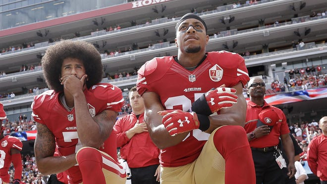 In this Oct. 2, 2016 file photo, San Francisco 49ers quarterback Colin Kaepernick, left, and safety Eric Reid kneel during the national anthem before an NFL football game against the Dallas Cowboys, in Santa Clara, Calif. Colin Kaepernick and Eric Reid have reached settlements on their collusion lawsuits against the NFL, the league said Friday, Feb. 19, 2019.