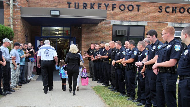 Akron police officers line the sidewalk as Charlee Winebrenner, enters kindergarten for the first in Coventry Township, Ohio on Thursday. Charlee's father Justin Winebrenner was fatally shot in November 2014.