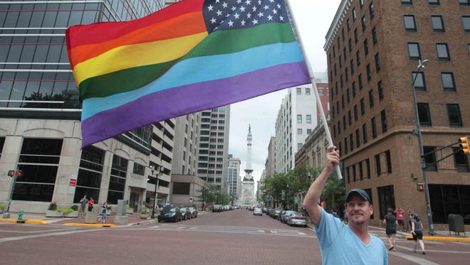 Ben Gleason waves a pride flag outside the Indiana Statehouse on June 26, 2013, as supporters of gay marriage rallied to support a court decision.