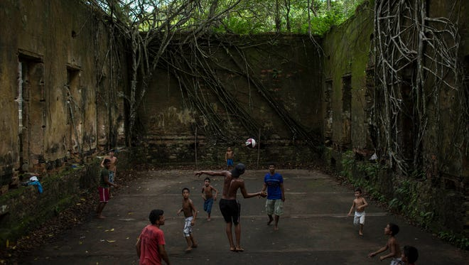 Children and adults play soccer in the ruins of Paricatuba, near Manaus, Brazil on May 21, 2014.