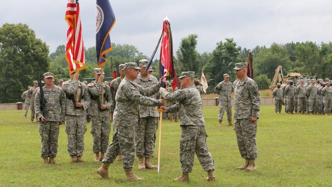 Col. John M. Epperly, far right, watches as Brig. Gen. Blake C. Ortner, the Virginia National Guard Land Component Commander, hands the unit colors for the Virginia National Guard's Staunton-based 116th Infantry Brigade Combat Team to Col. William J. Coffin signifying Coffin's assumption of command during a change of command ceremony held Aug. 2, 2014, at Fort A. P. Hill.
