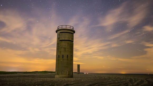 Fire-control towers along the beach in Cape Henlopen State Park near Gordon Pond are illuminated by the distant light of Rehoboth Beach and Dewey Beach on June 26.