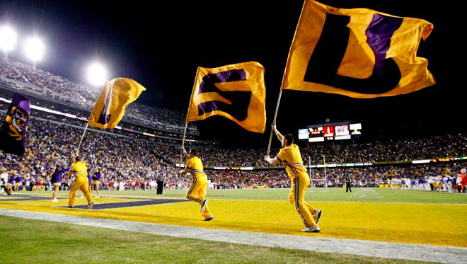 LSU Tigers cheerleaders carry a LSU flag following a touchdown in a game from 2012.