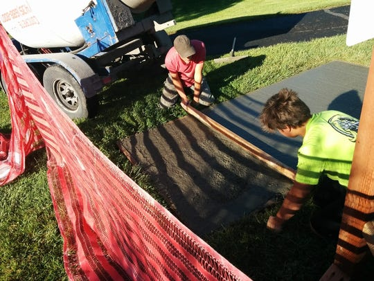 Workers put the finish touches on one of the concrete