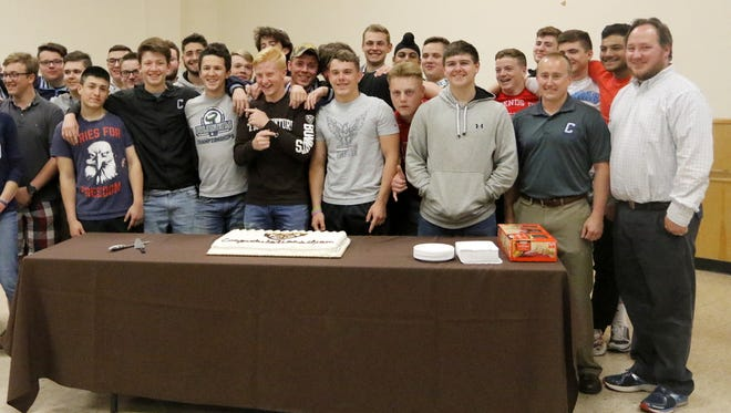 Corning-Painted Post senior Liam Phelan, front center in front of cake with St. Bonaventure shirt, poses for a photo with teammates, friends and coaches at his signing ceremony Wednesday at the Corning Local 1000 Union Hall.