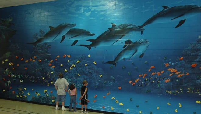 Artist Bradley J. Parrish's children, Andrew, Haley and Adam, check out his finished mural at County Line Elementary School in Germantown in 2004. The district will be tearing down the mural as part of a renovation and expansion.