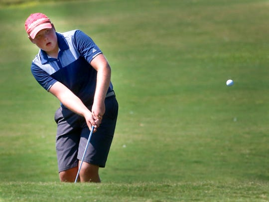 Oakland's Garrett Chumley chips his ball onto the green during the 7-AAA District Tournament, on Monday, Sept. 18, 2017, at Old Fort Park Golf Course.