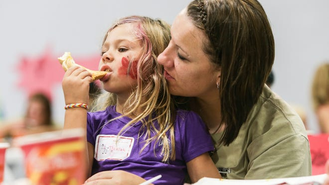 Inmate and mom, Tiffany Johnson, holds her daughter, Nevaeh Johnson, during lunch time at the Family Preservation Program's annual summer camp on Saturday, July 12, 2014, at the Indiana Women's Prison on Indianapolis' Westside.