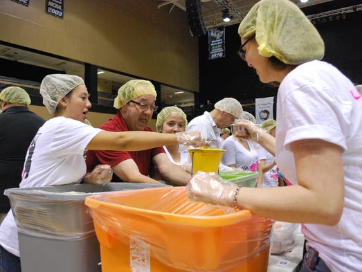 Volunteers pack boxes of dry food material at the annual