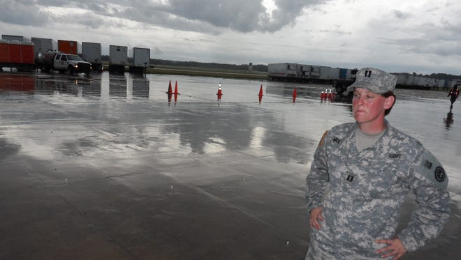 National Guard Capt. Sharon McDonald talks about working with FEMA at Esler Field to send meals and water to flood victims in South Louisiana. Behind her are trailers with hundreds of thousands of  Meals Ready to Eat and bottles of water.