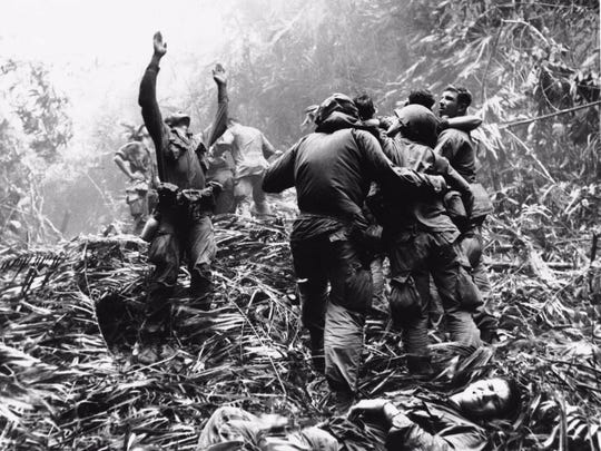 As fellow soldiers aid wounded buddies, a paratropper of A Company, 101st Airborne, guides a medical evacuation helicopter through the jungle foliage to pick up casualties during a patrol of Hue, South Vietnam, in April 1968.