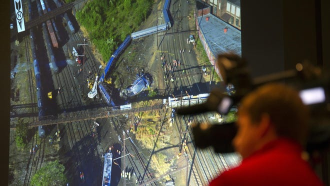 A photograph is displayed on a video monitor of the derailment of Amtrak passenger train in Philadelphia last year during a National Transportation Safety Board (NTSB) meeting on the derailment, Tuesday, May 17, 2016, in Washington. (AP Photo/Cliff Owen)