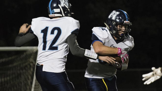 MMU's Asa Carlson (12) hands the ball off to Raymond Wilson (32) during the high school football game between the Mount Mansfield Cougars and the Burlington Seahorses at Buck Hard Field on Friday night.