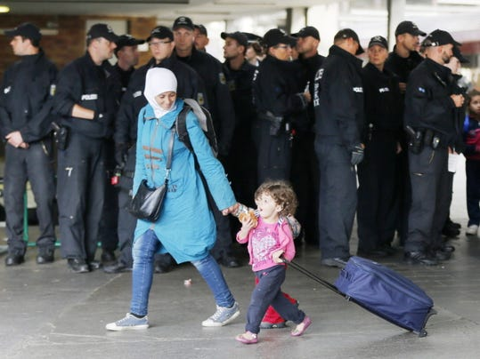 Refugees pass police officers as they arrive Saturday at the main train station in Munich, southern Germany.