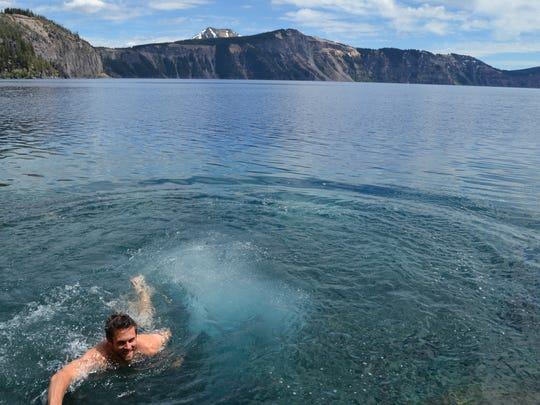 Tyler Dodds swims back to shore after jumping into the icy cold waters of Crater Lake.