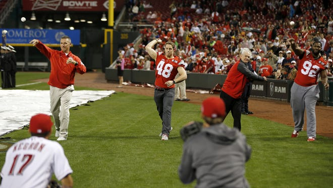 (Left to right) Ohio State football coach Urban Meyer, linebacker Joe Burger, a La Salle High School alumnus; Ohio State assistant coach Kerry Coombs and defensive lineman Adolphus Washington, a Taft High School alumnus, throw out the ceremonial first pitch ahead of the Reds' Opening Night game against the Pittsburgh Pirates on April 8.