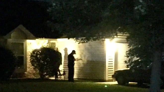 Porch lights illuminate an investigator at the Greenwood home where police say a robbery suspect was killed and two residents were injured in a shoot out about 12:30 a.m. Sept. 12, 2017.