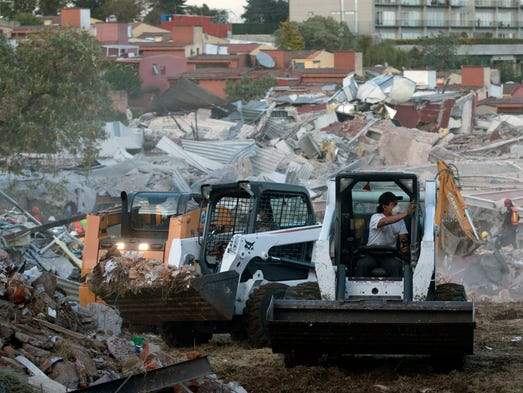 Rescue workers move rubble as the search for survivors
