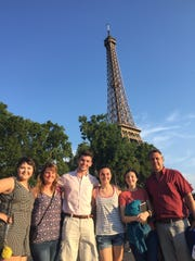 The McGlaughlin family poses in front of the Eiffel