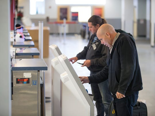 People check in for their flight at the American Airlines