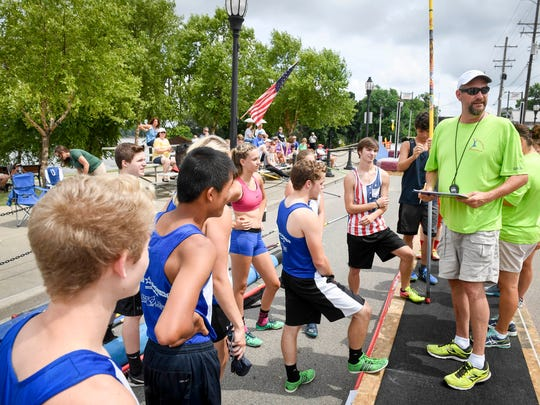 "High school pole vaulters check in with Pat Rowland before the start of the Group ""B"" competition at the 11th annual Jammin' & Jumpin' Street Vault event at the Henderson riverfront Tuesday, July 4, 2017."