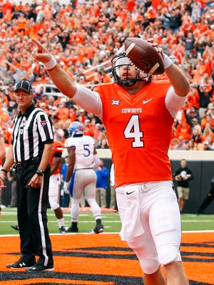 Oklahoma State Cowboys quarterback J.W. Walsh (4) celebrates after scoring a touchdown against Kansas Jayhawks during the first quarter at Boone Pickens Stadium.