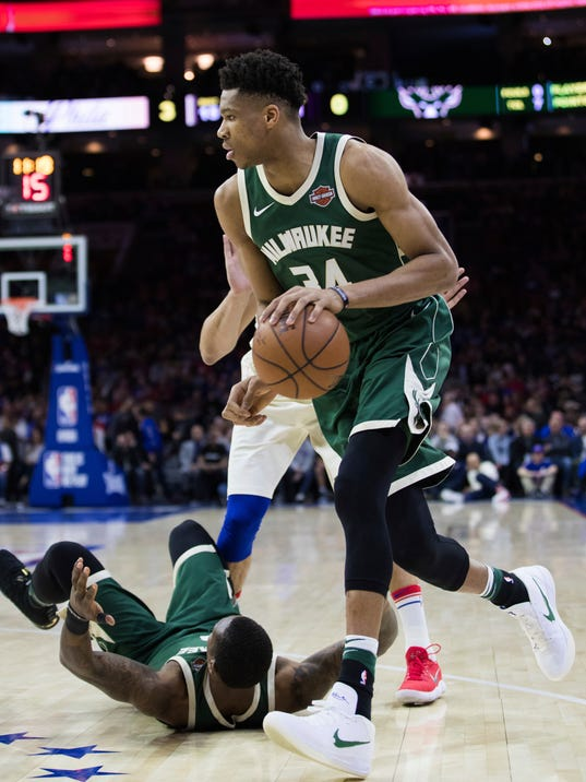 Milwaukee Bucks' Giannis Antetokounmpo, right, of Greece, drives to the basket as teammate Eric Bledsoe, left, hits the floor during the first half of an NBA basketball game against the Philadelphia 76ers, Wednesday, April 11, 2018, in Philadelphia. (AP Photo/Chris Szagola)