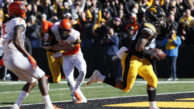 Iowa running back Tyler Goodson, right, scores on a 2-yard touchdown run ahead of Illinois defensive back Stanley Green, left, during the first half of a game on Saturday, Nov. 23, 2019, in Iowa City, Iowa.