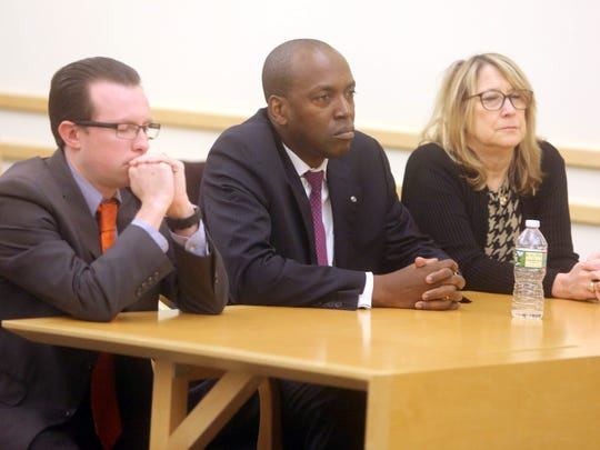 Spring Valley Trustee Vilair Fonvil, center, listens