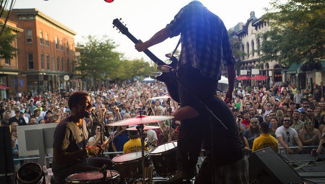 Austin Humphreys/The Coloradoan In the Whale guitarist Nate Valdez is lifted in the air by Brandon Whalen as they perform on Linden Street during Bohemian Nights at NewWestFest on Aug. 13, 2016. In the Whale guitarist Nate Valdez is lifted in the air by Brandon Whalen as they perform on Linden Street during Bohemian Nights at NewWestFest Saturday, August 13, 2016.