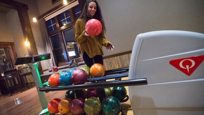 Ali Fitzgerald bowls a round at the in-house bowling lanes at the Trails at Timberline apartments on Thursday, February 22, 2018.